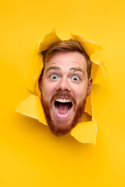 Cara espantado com barba ruiva olhando para a câmera e gritando enquanto espia pelo buraco no papel amarelo rasgado Foto Premium