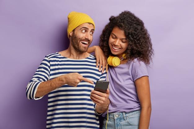 Cara feliz de chapéu amarelo e macacão listrado, explica para a garota afro como usar o novo aplicativo do smartphone, aponta no display, fica perto, não imagina a vida sem as tecnologias modernas. Foto gratuita