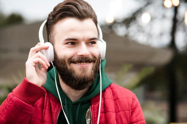 Cara feliz de close-up com fones de ouvido e jaqueta vermelha Foto gratuita