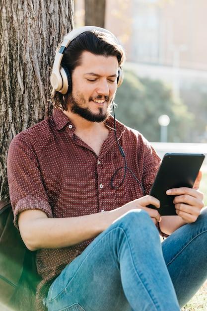 Cara feliz usando um telefone inteligente para ouvir música com fones de ouvido Foto gratuita