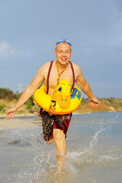 Cara gay corre na água com um anel de borracha amarelo Foto Premium