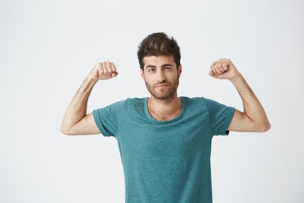 Cara hispânica esportiva jovem de camiseta azul e penteado elegante, mostrando brincando com os músculos posando para sessão de fotos de revista de esporte. Foto gratuita