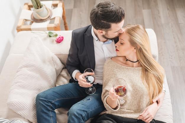 Cara jovem beijando na frente da senhora com taças de vinho e sentado no sofá na sala Foto gratuita