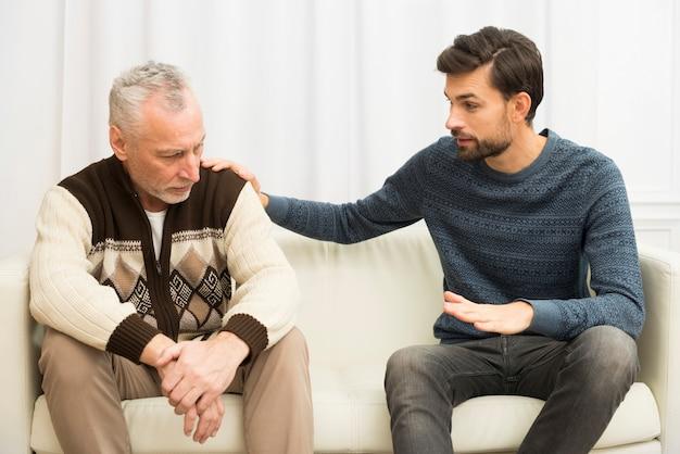 Cara jovem, com a mão no ombro do homem triste envelhecido no sofá Foto gratuita