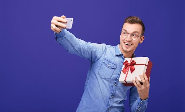 Cara jovem com presente na mão, fazendo selfie. Foto Premium