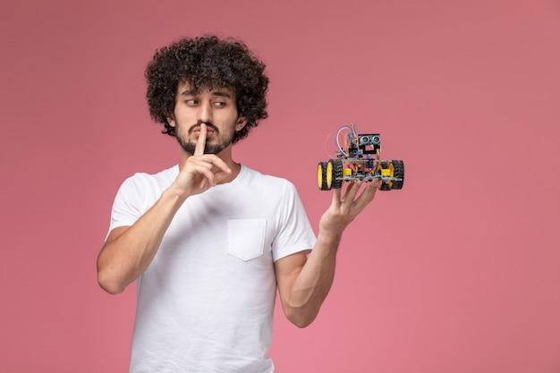 Cara jovem de frente mostrando gesto de silêncio e robô eletrônico Foto gratuita