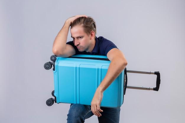 Cara jovem e bonito viajante parado com uma mala estressante, mantendo as mãos na cabeça cansada e frustrada sobre um fundo branco Foto gratuita