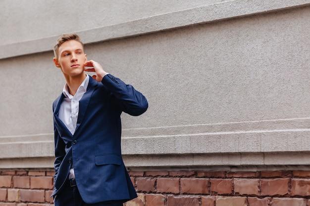 Cara jovem e elegante, com um rosto monumental caminha em uma cidade legal perto das paredes de madeira e pedra Foto Premium