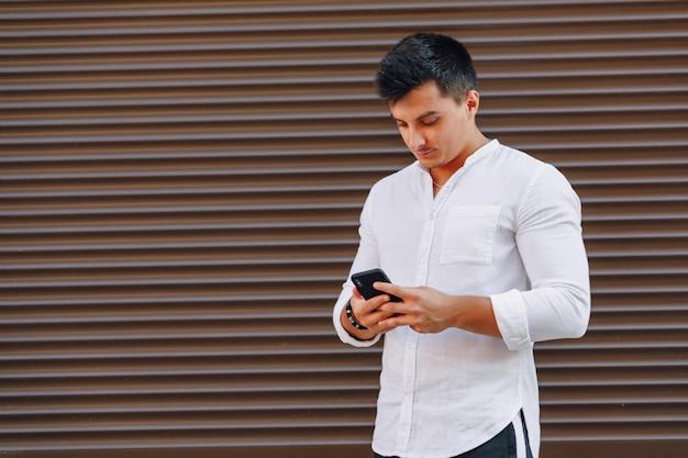 Cara jovem elegante na camisa digitando no telefone no fundo simples Foto Premium