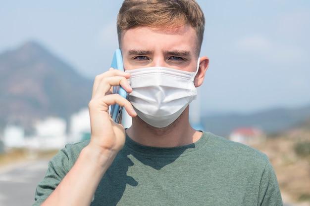 Cara, jovem em máscara médica estéril protetora no rosto chamando ambulância, falando no celular ao ar livre. conceito de coronavírus Foto Premium