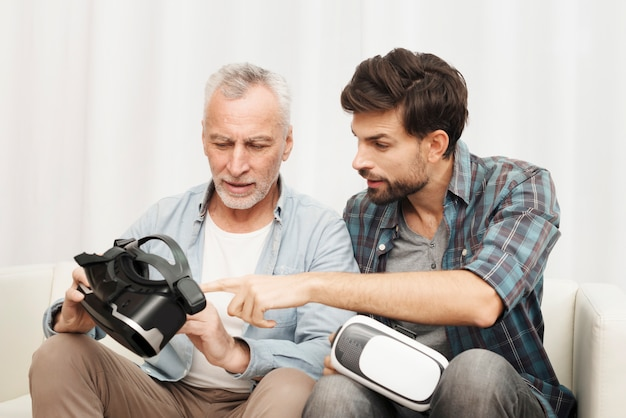 Cara jovem, explicando ao homem envelhecido sobre óculos vr no sofá Foto gratuita