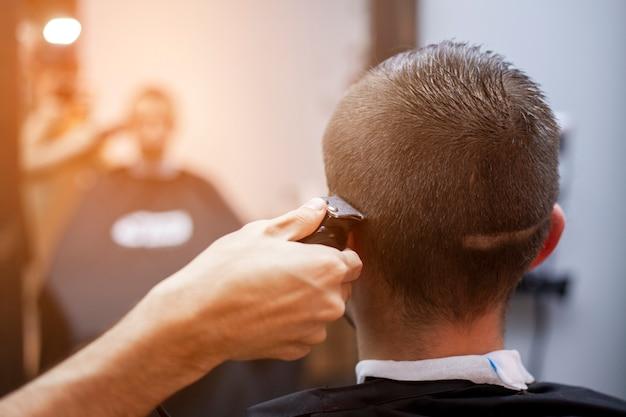 Cara jovem faz um corte de cabelo curto em uma barbearia com um aparador, close-up Foto Premium