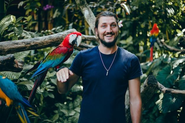 Cara jovem posando em um zoológico com um papagaio na mão, um homem barbudo e um pássaro Foto gratuita