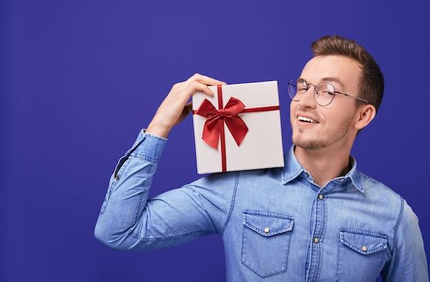 Cara jovem sorridente em camisa jeans com presente na mão. natal, ano novo, dia dos namorados. Foto Premium