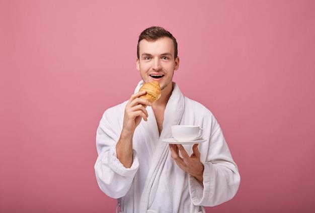 Cara legal alegre em roupão branco está de pé na parede de volta com croissant perfumado Foto Premium