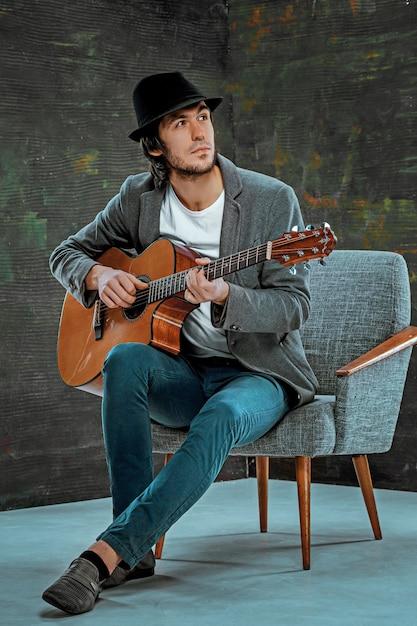 Cara legal com chapéu tocando guitarra em fundo cinza Foto gratuita