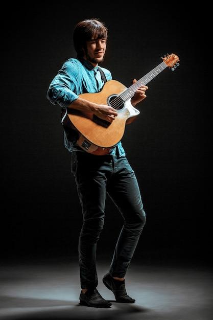 Cara legal em pé com a guitarra em fundo escuro Foto gratuita