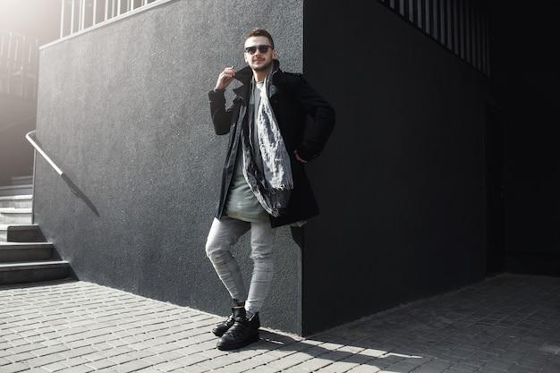 Cara legal em roupas elegantes do lado de fora, inclinando-se para a parede. Foto gratuita