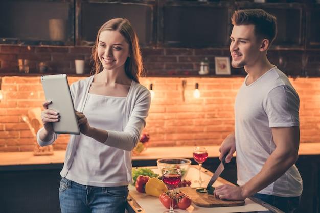 Cara na cozinha, enquanto sua namorada está mostrando tablet. Foto Premium