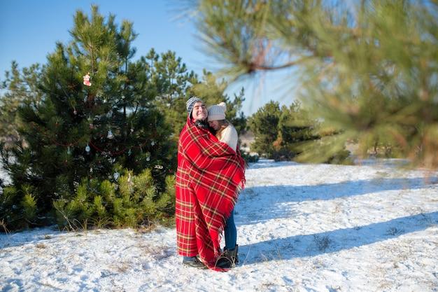 Cara no cobertor xadrez vermelho envolve a menina para que ela se aqueça Foto Premium
