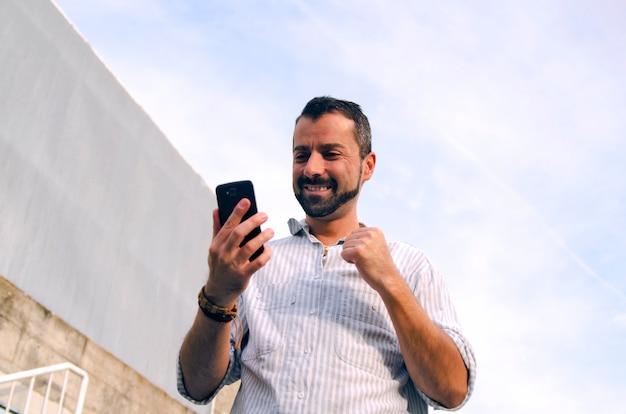 Cara, olhando para o celular, feliz lendo boas notícias. homem recebe resposta positiva em inteligente pho Foto Premium