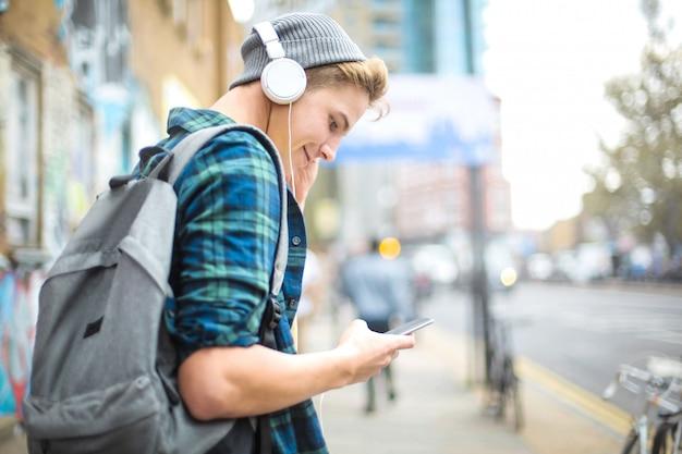 Cara ouvindo música com fones de ouvido enquanto caminhava na rua Foto Premium