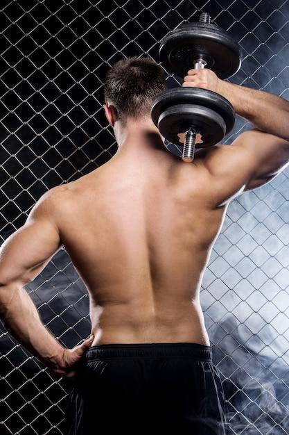 Cara poderoso com um halteres mostrando os músculos na cerca Foto gratuita