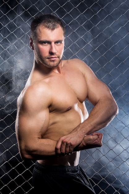 Cara poderoso com uma corrente mostrando seus músculos Foto gratuita