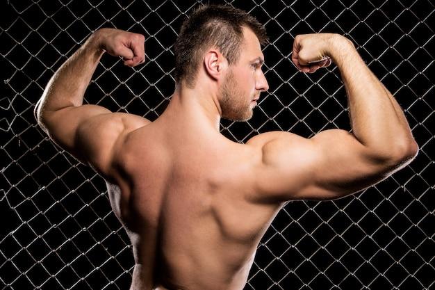 Cara poderoso, mostrando seus músculos na cerca Foto gratuita
