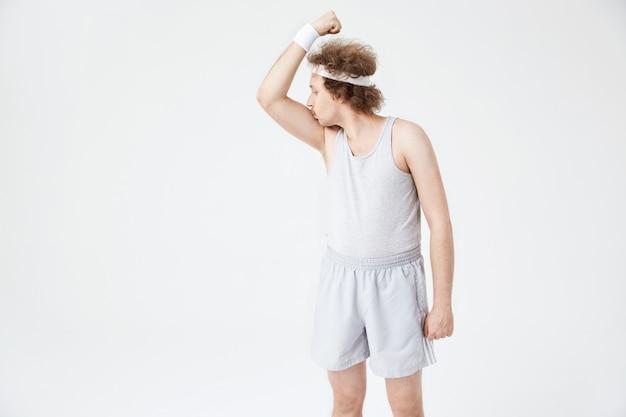 Cara retrô com bandana branca beijando o bíceps do braço direito Foto gratuita