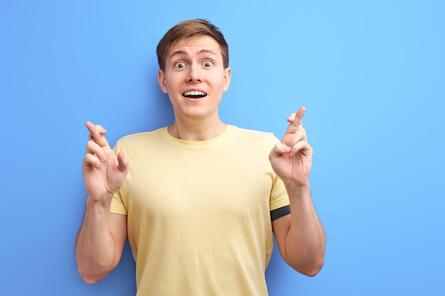 Cara segurando os dedos cruzados, esperando por melhores e bons resultados. conceito de boa sorte. fundo azul isolado no estúdio. pessoas, conceito de emoções humanas Foto Premium
