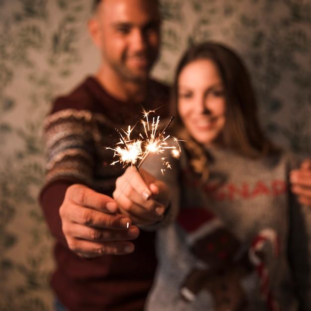 Cara sorridente, abraçando a senhora alegre com luzes de bengala em chamas Foto gratuita