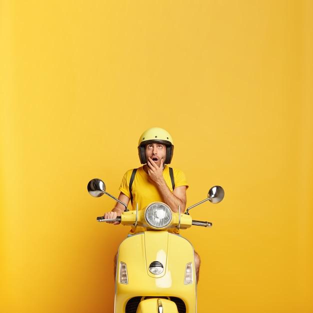 Cara surpreso com capacete dirigindo uma scooter amarela Foto gratuita