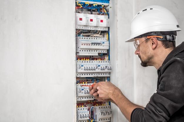 Cara, um eletricista trabalhando em uma central telefônica com fusíveis. instalação e conexão de equipamentos elétricos. Foto gratuita