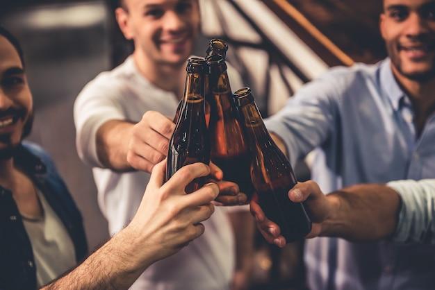 Caras bonitos estão tinindo garrafas de cerveja e sorrindo. Foto Premium
