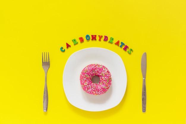 Carboidratos de texto, donut rosa na placa e garfo de faca de mesa de talheres dieta insalubre Foto Premium