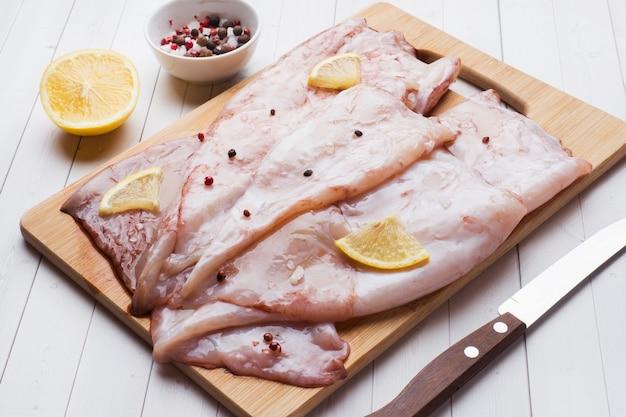 Carcaça crua do calamar com as especiarias e o limão prontos para cozinhar na tabela. Foto Premium