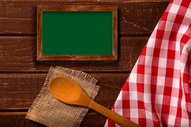 Cardápio do restaurante. vista superior do menu de quadro-negro deitado sobre a mesa de madeira rústica com colheres e guardanapo vermelho. vista superior. Foto Premium