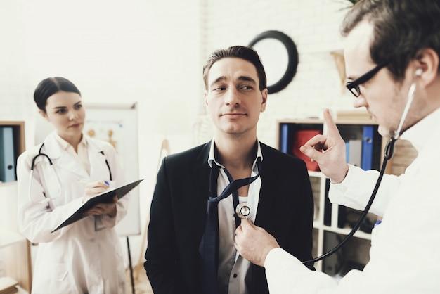 Cardiologista qualificado ouvindo o batimento cardíaco do paciente. Foto Premium