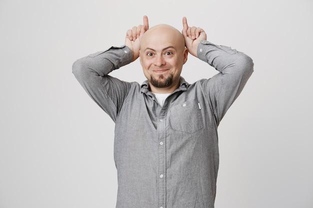 Careca bobo e engraçado mostrando chifres atrás da cabeça Foto gratuita