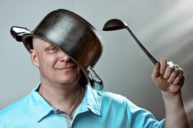 Careca com uma panela na cabeça e uma concha na mão Foto Premium