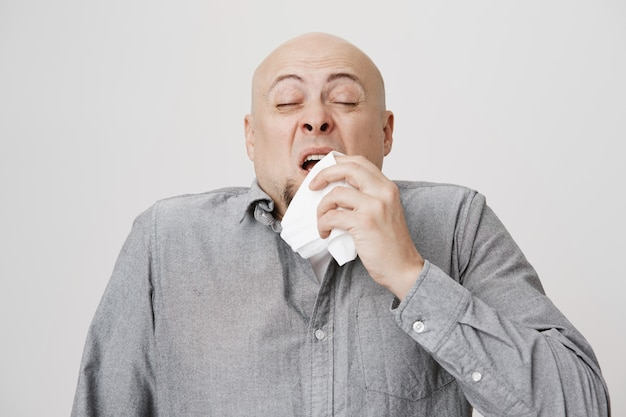 Careca doente de meia-idade espirrando em um guardanapo Foto gratuita