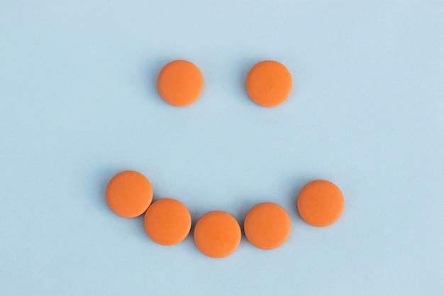 Caretas de comprimidos alaranjados sobre um fundo azul. conceito de antidepressivos Foto Premium