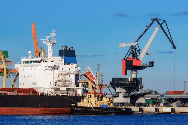 Cargueiro preto atracado no porto com apoio de rebocador Foto Premium