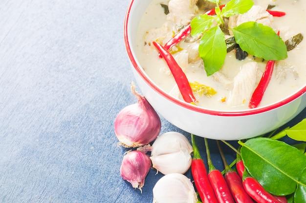 Caril de frango verde com ingrediente picante cru comida tailandesa tradicional sobre fundo azul claro Foto gratuita
