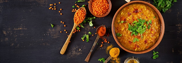 Caril picante indiano dhal na tigela, especiarias, ervas, mesa de madeira preta rústica. Foto gratuita