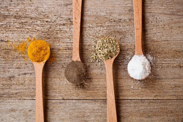 Caril, pimenta, orégano e sal de cozinha em colheres de madeira Foto Premium