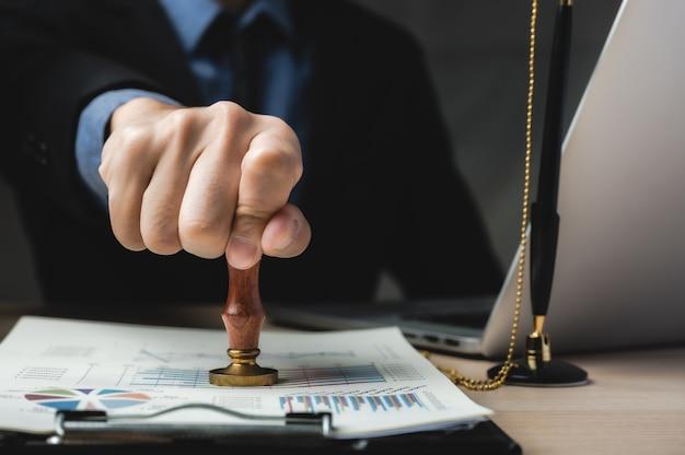 Carimbo da mão da pessoa com carimbo aprovado no documento de marketing empresarial na mesa de um escritório moderno Foto Premium