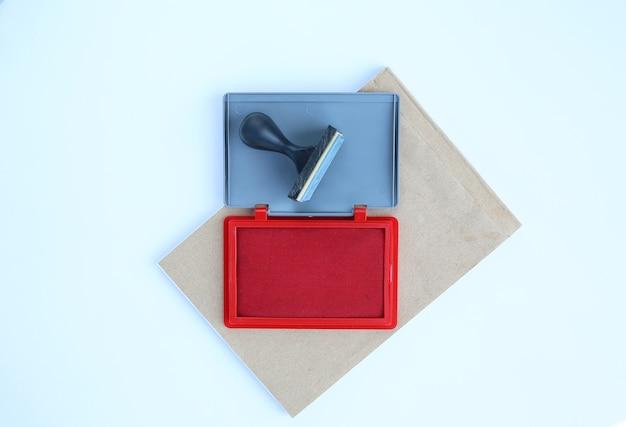 Carimbo de borracha e cartuchos de tinta vermelhos no livro marrom contra o fundo branco. Foto Premium
