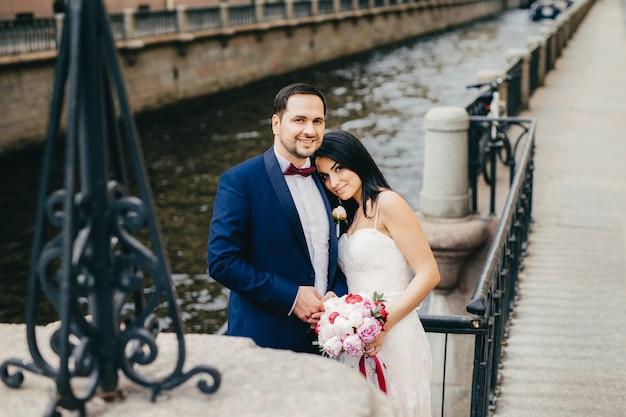 Carinhoso casal apaixonado comemorar seu casamento, posar para a câmera como ficar perto da ponte e do rio Foto Premium
